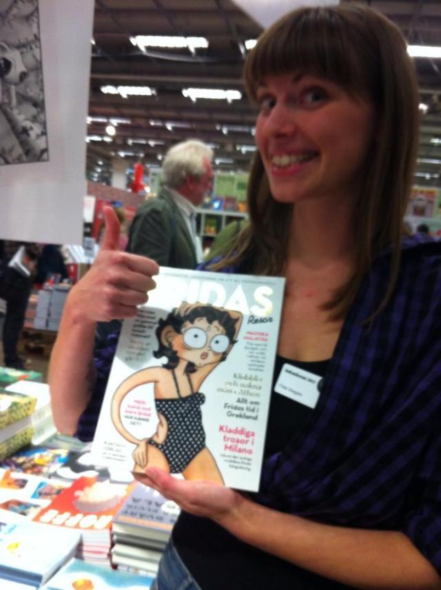 Fridas resor håller upp boken på bokmässan